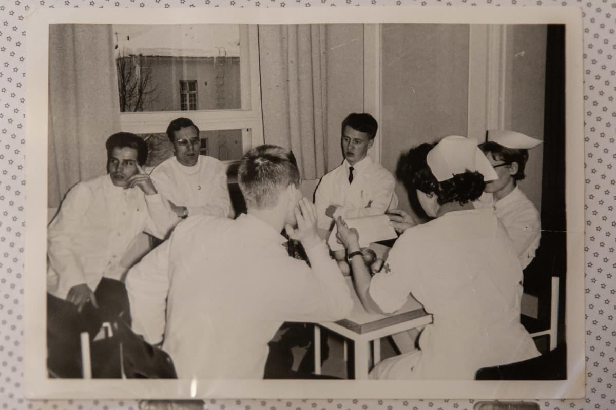 Matti Hjerppe ja muita hoitajia pöydän ääressä Rauhan sairaalassa. Kuva otettu n. vuonna 1973.