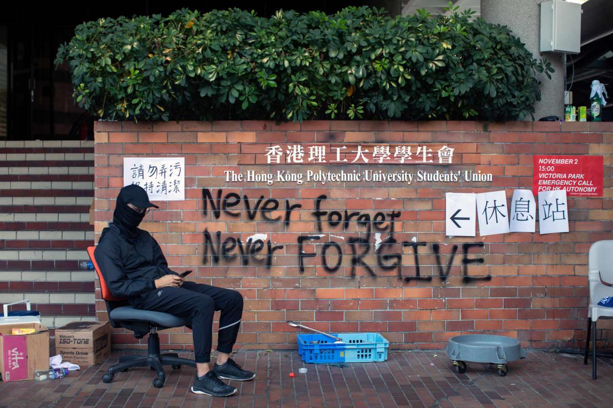 Naamioitunut opiskelija istuu seinäkirjoituksen vieressä. Englanninkielinen teksti on Never forget, never forgive.