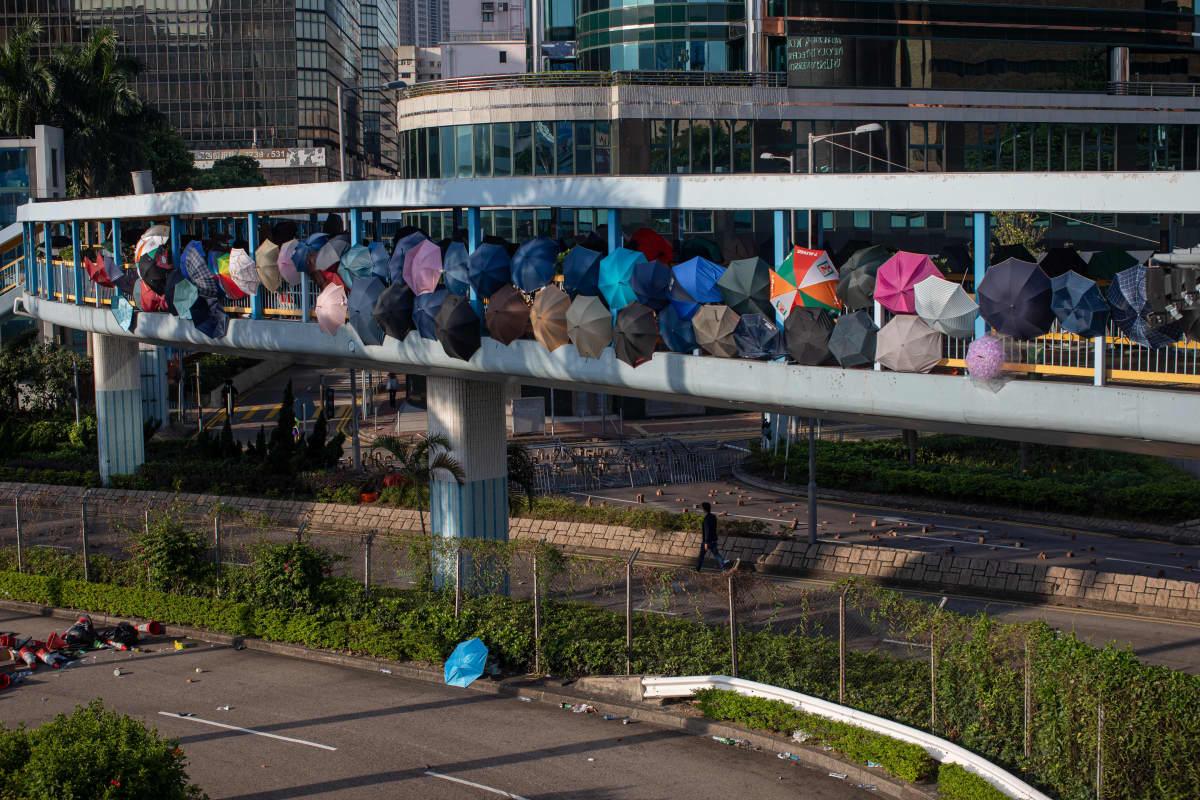 Ylikulkusillalle ryhmittyneet ihmiset suojautuvat suurella määrällä sateenvarjoja.