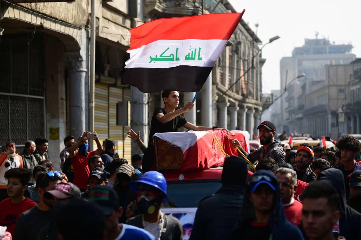 Ihmisiä kantamassa arkkua. Nuorukainen heiluttaa Irakin lippua.