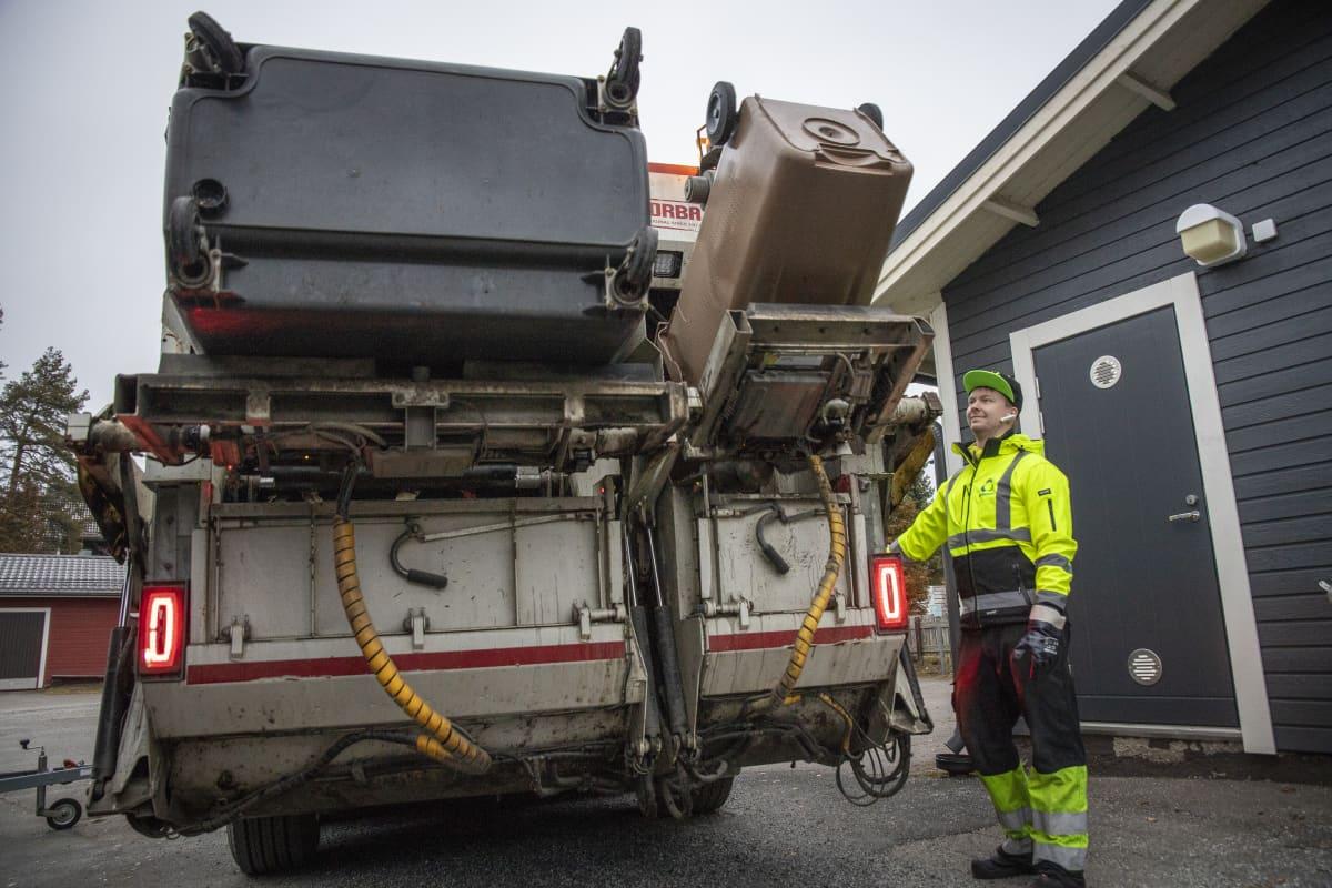 Tomi Tuononen tyhjentää Jätekukon roska-astioita roska-autoon.