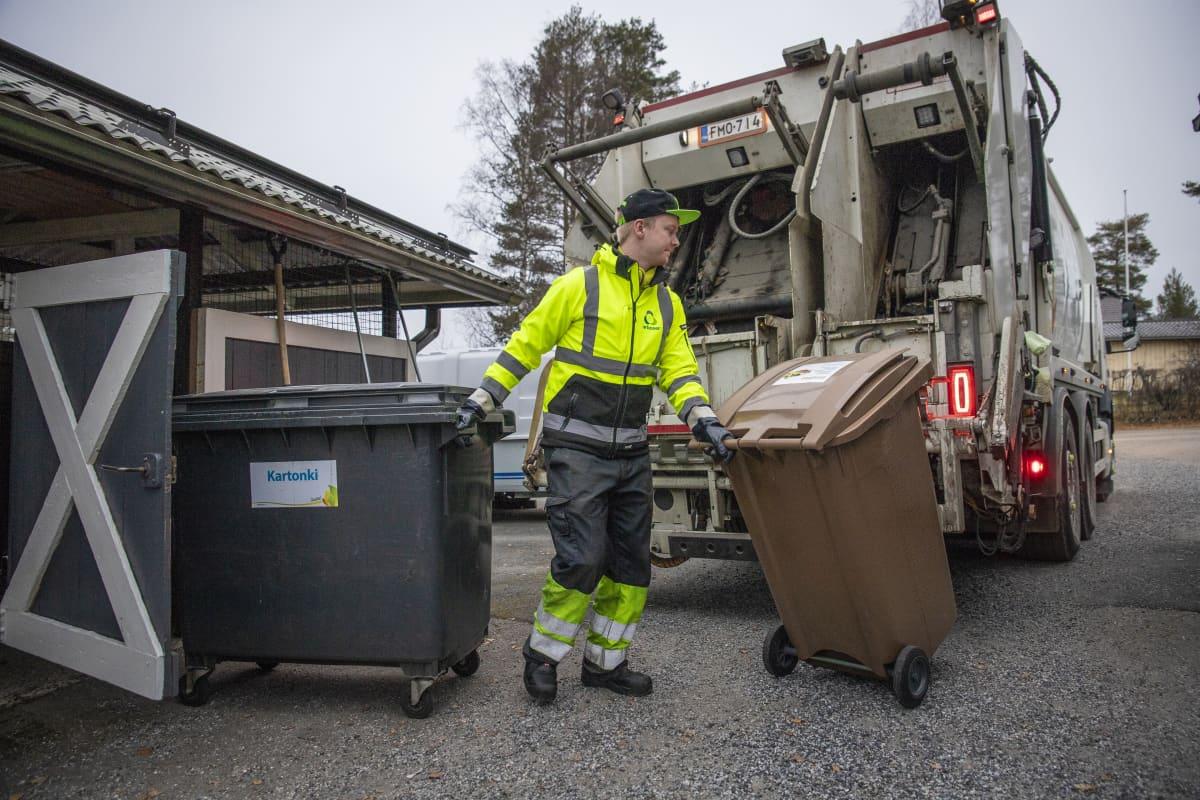 Tomi Tuononen tyhjentää Jätekukon roska-asitoita roska-autoon.