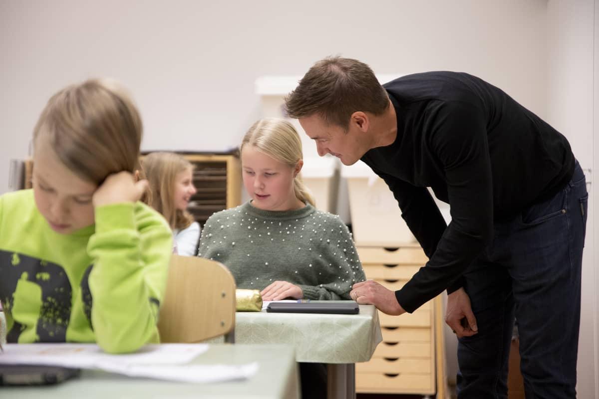 Ilkka Paananen juttelee oppitunnilla tytön kanssa.