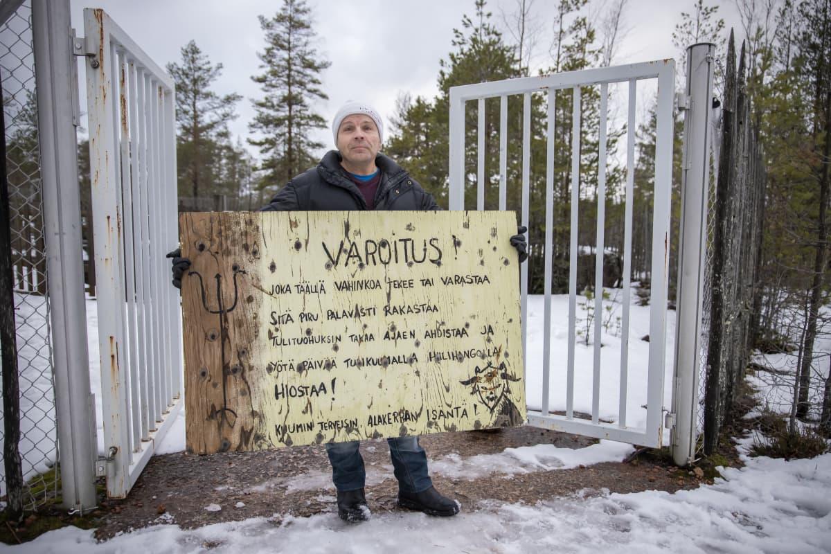 Keijo Haanpää pitää varoituskylttiä kädessään.