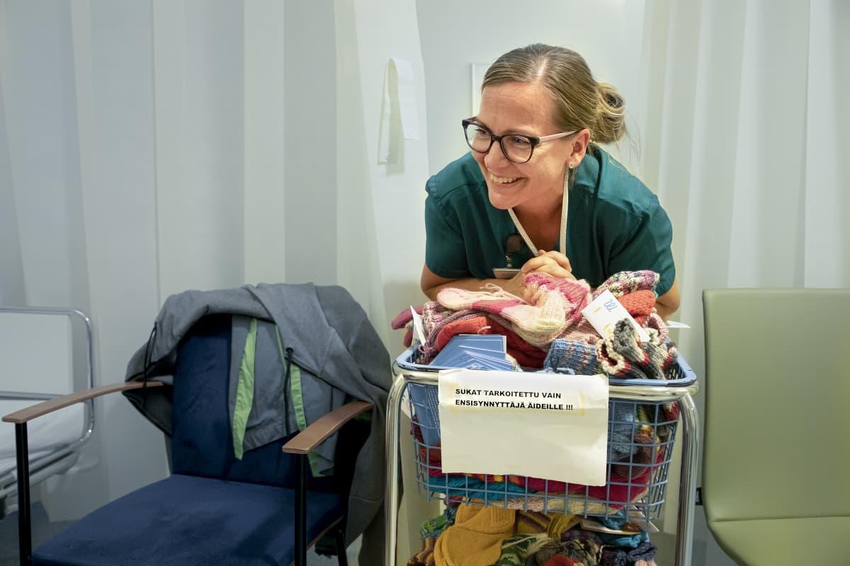 Kätilö nojaa kärryyn, jossa on Marttojen ensisynnyttäjille neulomia villasukkia.
