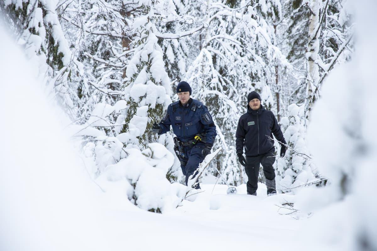 erätarkastaja Tobias Peura ja vanhempi konstaapeli Kimmo Örn etsivät susien jälkiä lumisessä metsässä