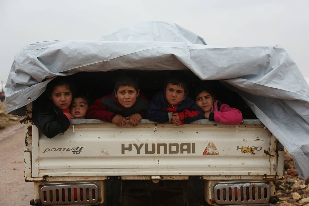 Syyrialaislapsia kuljettava auto matkasi 28. joulukuuta pois levottomuuksien keskelle joutuneesta Maarat al-Numanin kaupungista.
