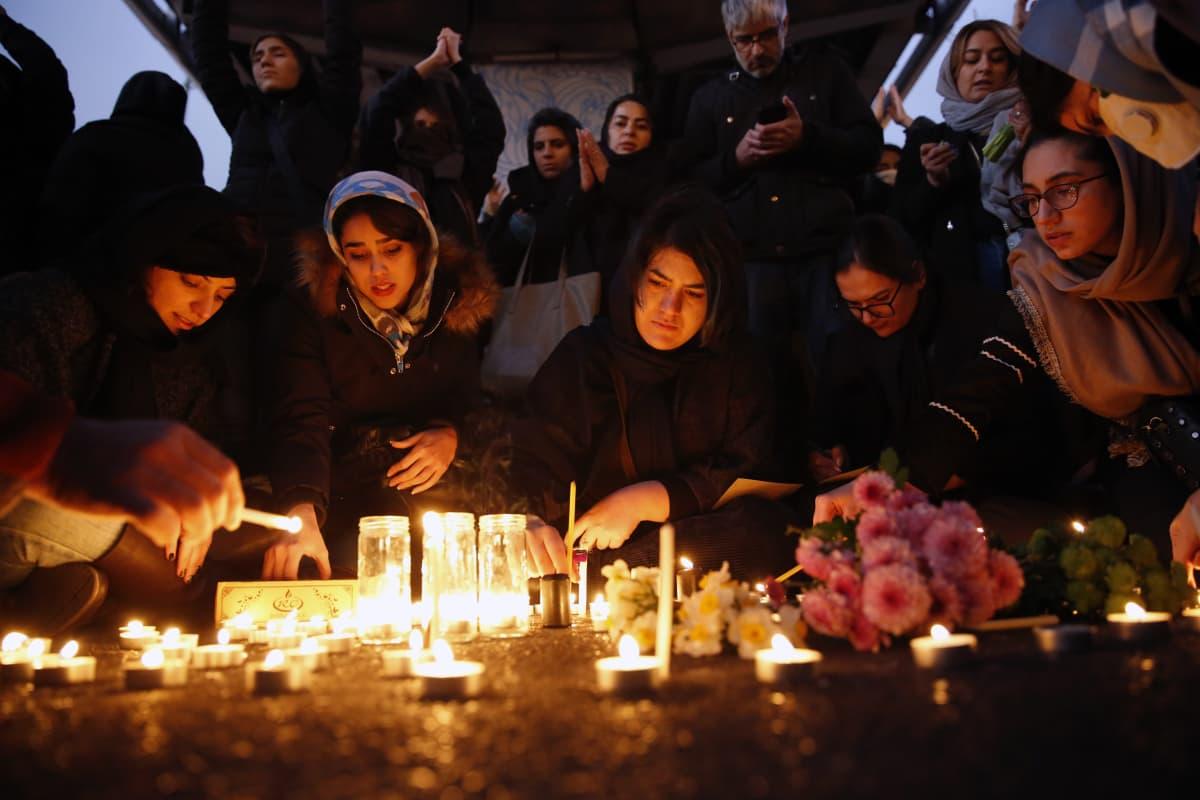 Naiset ovat kokoontuneet muistokynttilöiden äärelle.