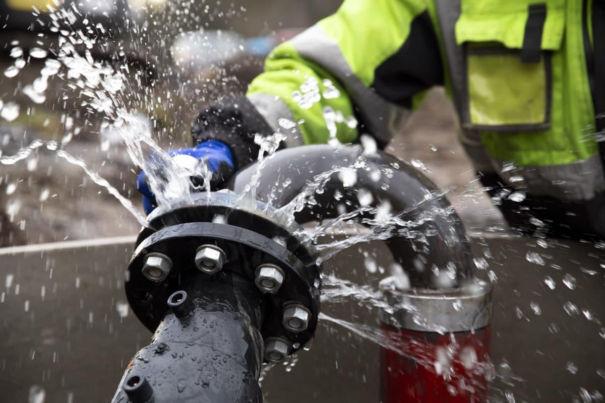 Vettä roiskuaa putkiliitoksesta.