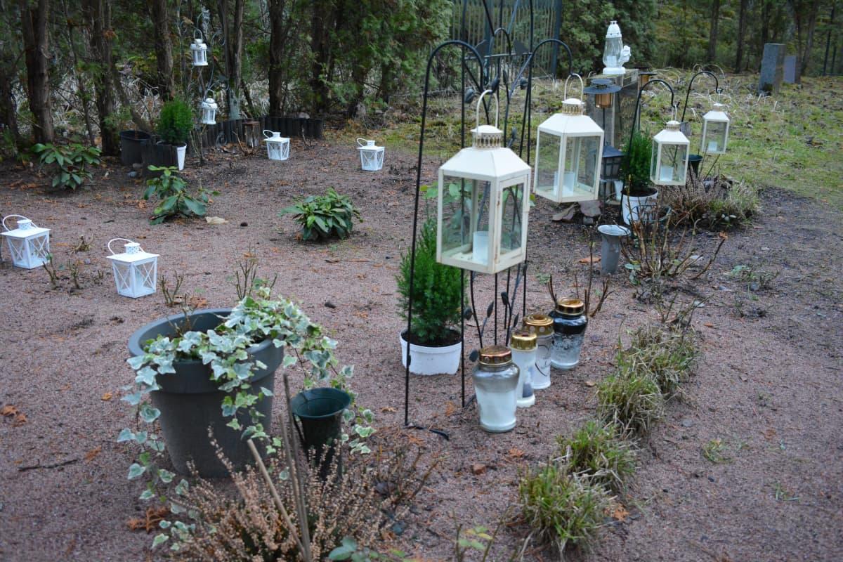 Kynttilöitä ja muistoesineitä pienellä hautausmaalla.