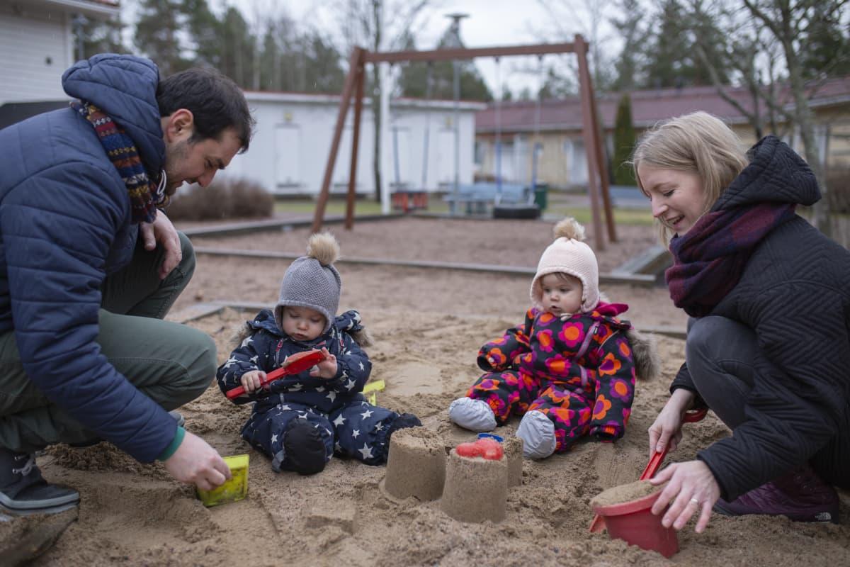 Henna Kapulainen ja Pasquale Romano kaksostensa Mian ja Leon kanssa hiekkalaatikolla.