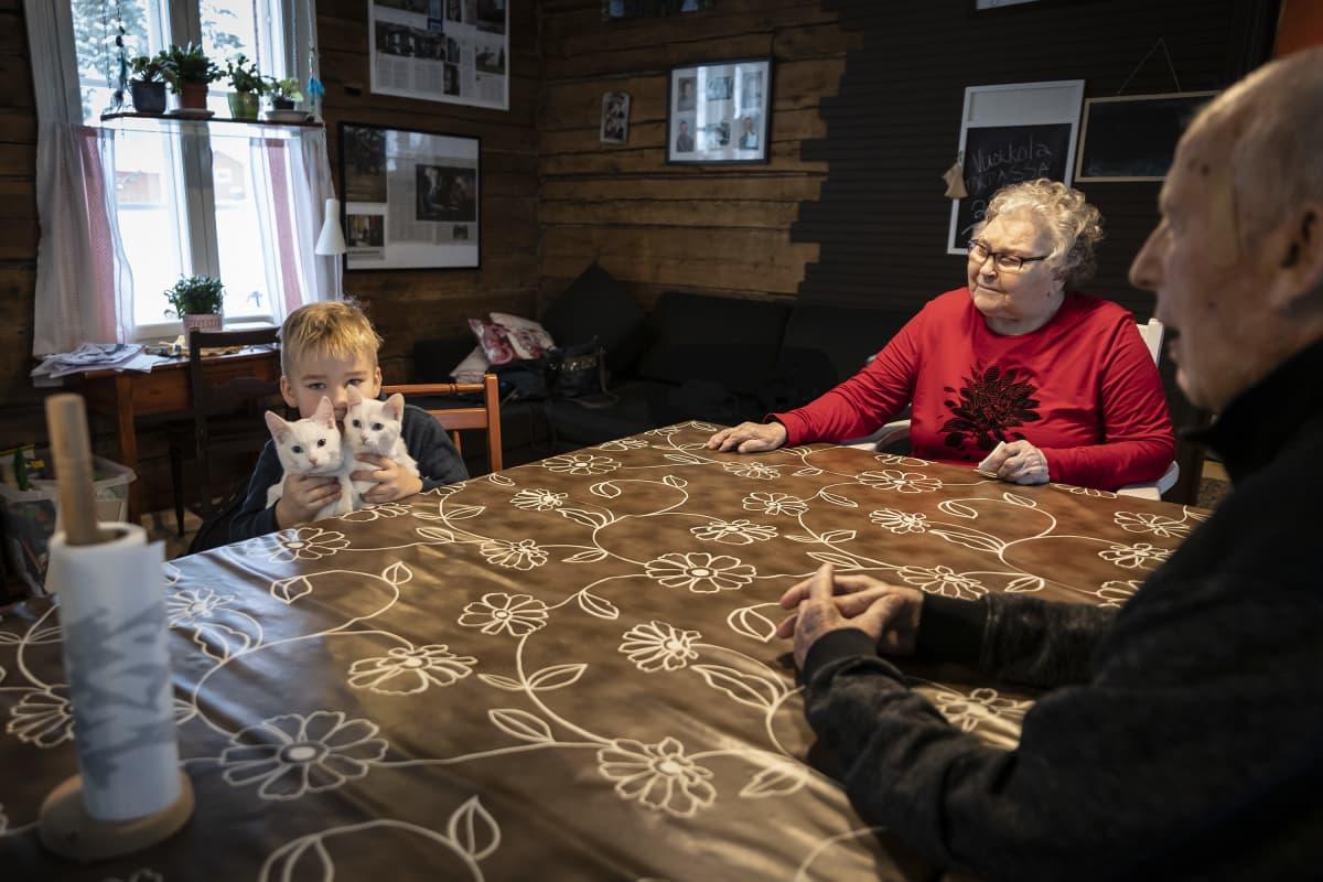 Vasemmalla lapsi pitelee kahta valkoista kissaa sylissään ja istuu pöydän ääressä. Oikealla kaksi vanhusta saman pöydän ääressä istumassa.