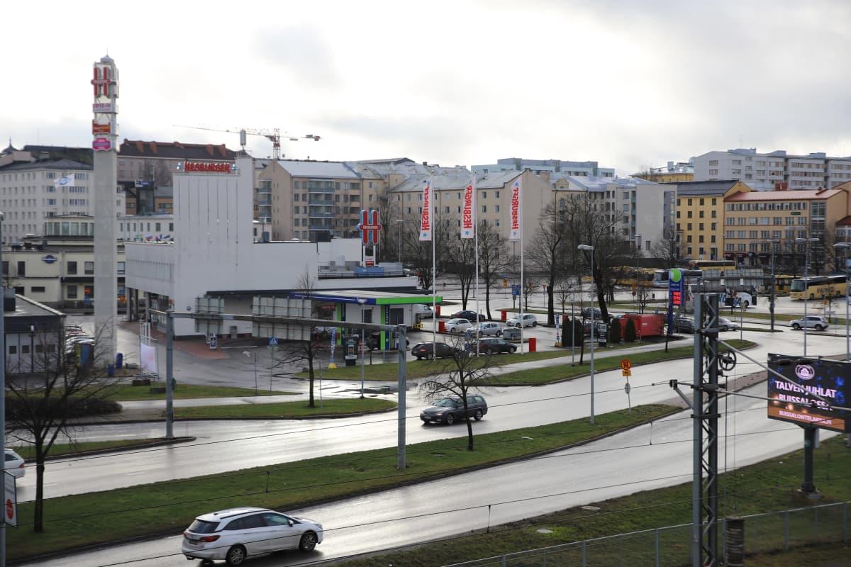 autoja tiellä, taustalla linja-autoterminaali