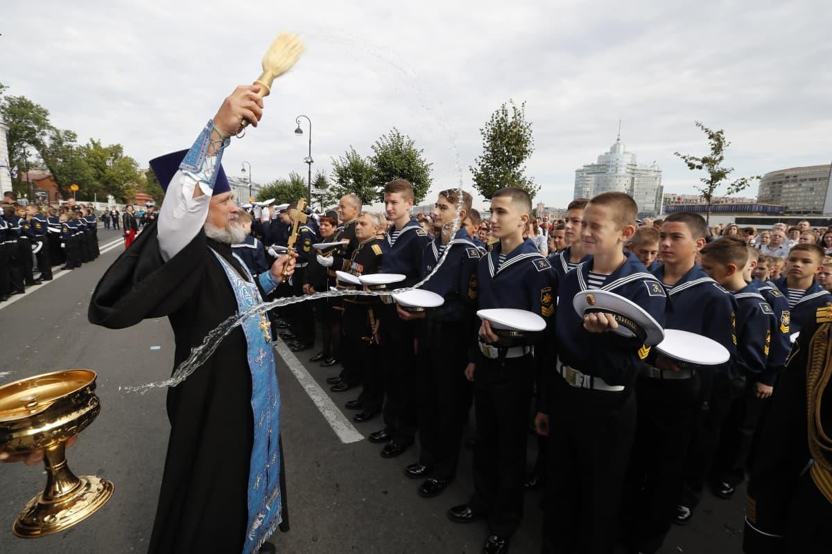 Pappi heittää vettä sotilaiden päälle.