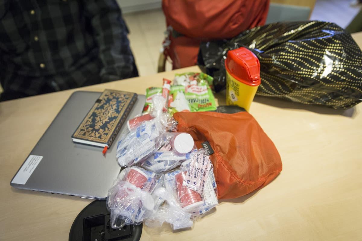 Tukialushankeen, projektipäällikön Robet Kosken reppu sisältää tarvikkeita asunnottomille mm kondomeja, puhtaiata neuloja ja lakritsia