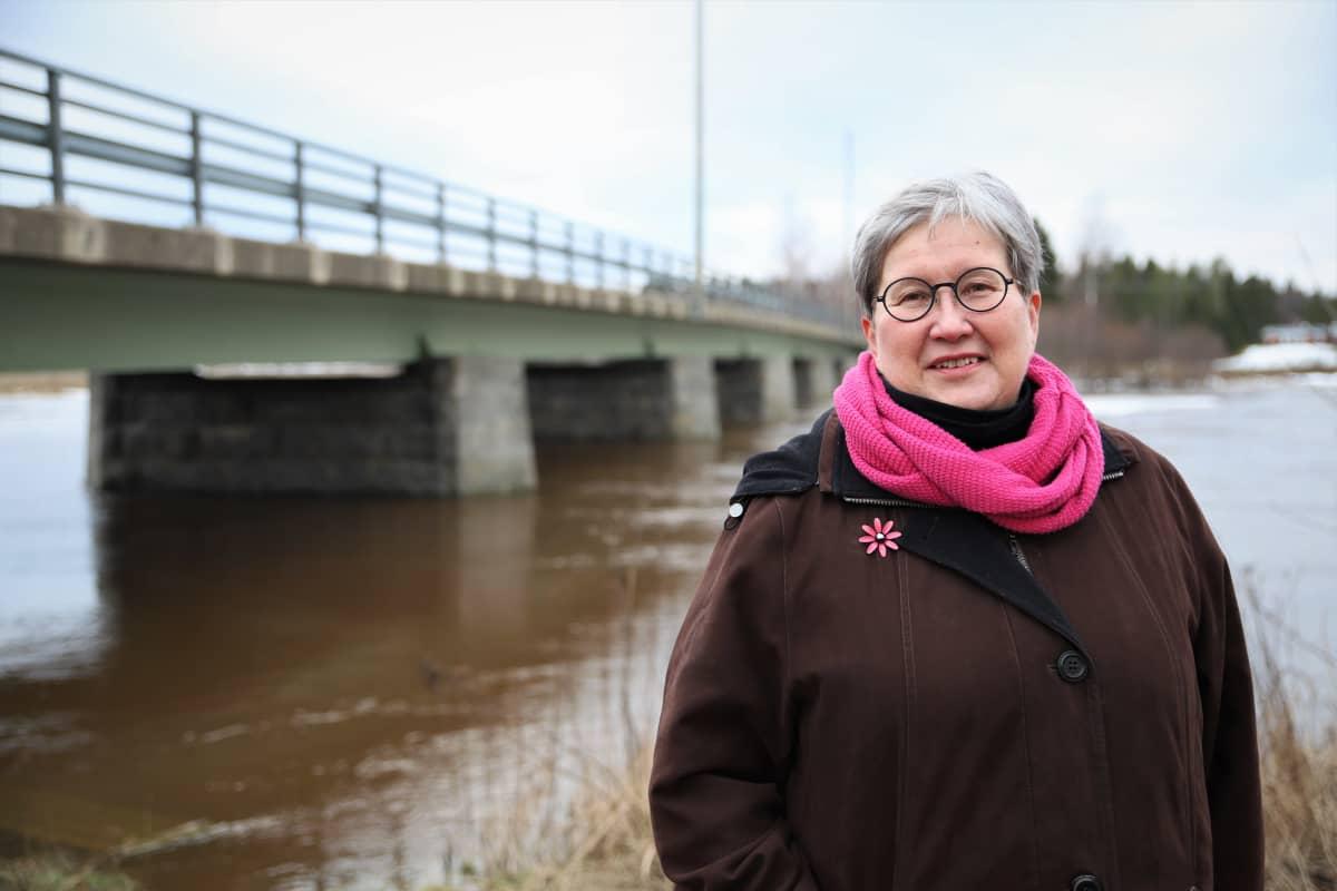 Liisa Maria Rautio seisoo Skatilan sillan edessä Mustasaaren Veikkolassa.