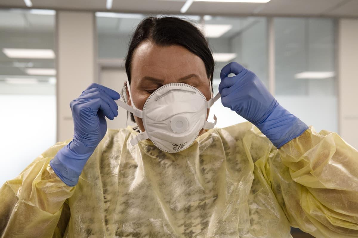 Nainen asettaa hengitysmaskia kasvoilleen