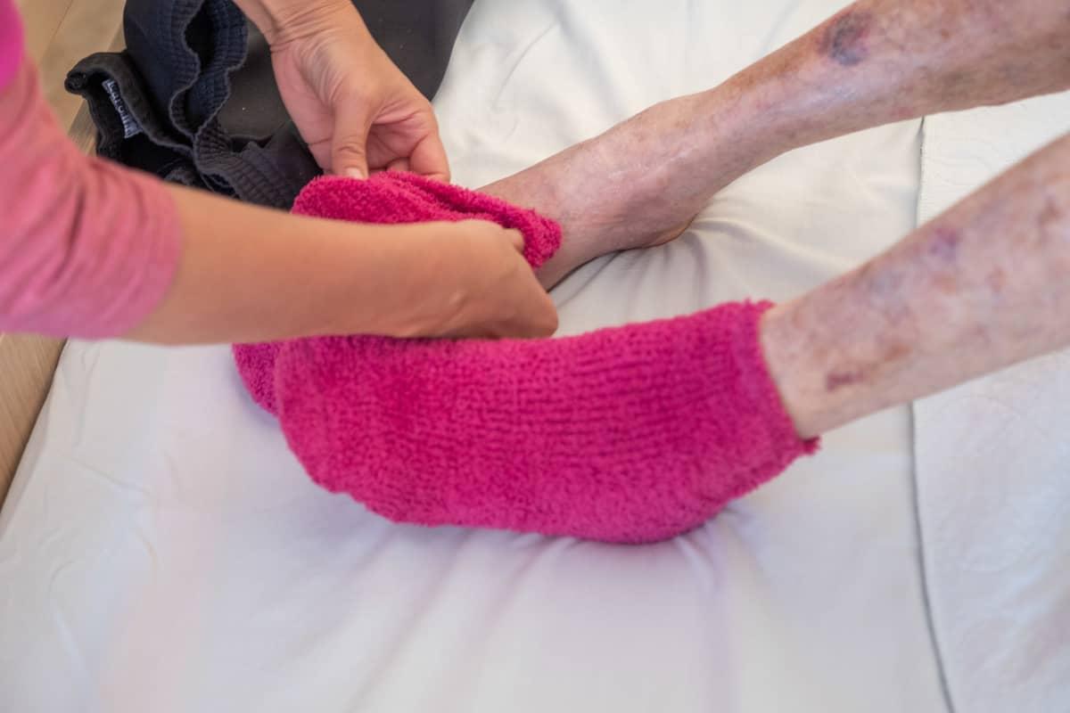Hoitaja pukee vanhukselle sukkia.