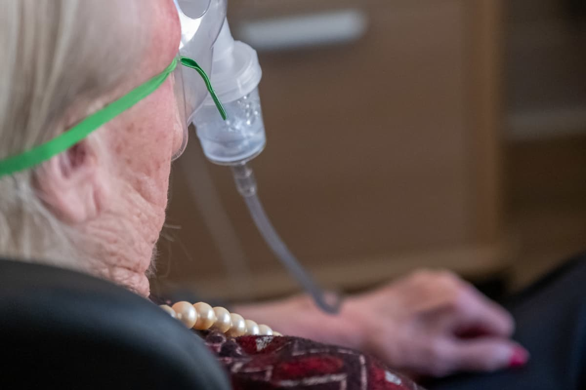 Lähikuva vanhuksesta takaapäin. Vanhuksella happimaski, jolla hän ottaa keuhkolääkettä.