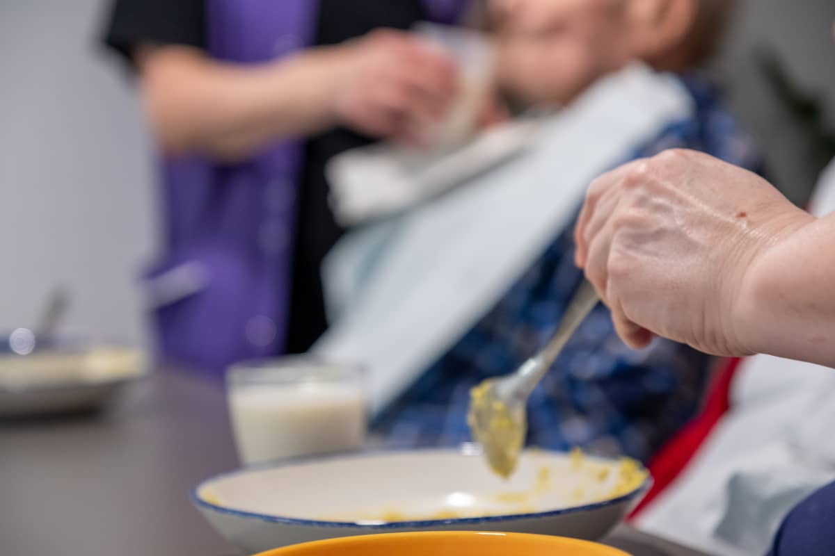 Hoitajat syöttää vanhuksia Myyrmäen vanhustenkeskuksessa.