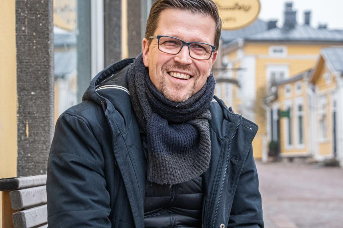 Klaus Härö sitter på en bänk och är glad