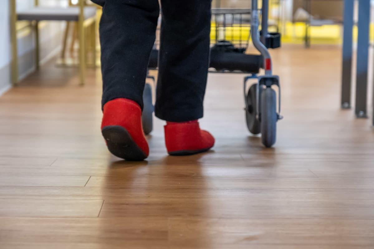 Lähikuva vanhuksesta, joka kävelee rollaattorin kanssa.