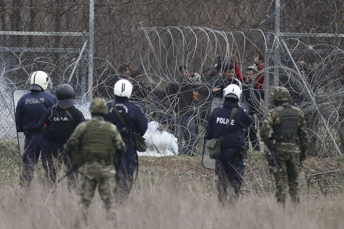 Kreikkalaisia poliiseja piikkilanka-aidan edessä, toisella puolella Turkista pyrkiviä siirtolaisia.