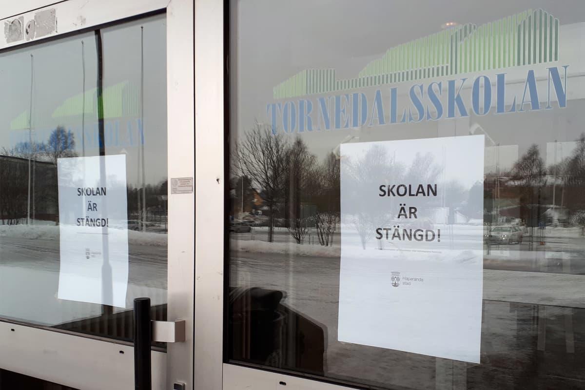 Tornedalsskolanin ovessa kyltti, jossa kerrotaan ruotsiksi koulun olevan suljettu koronaviruksen vuoksi.