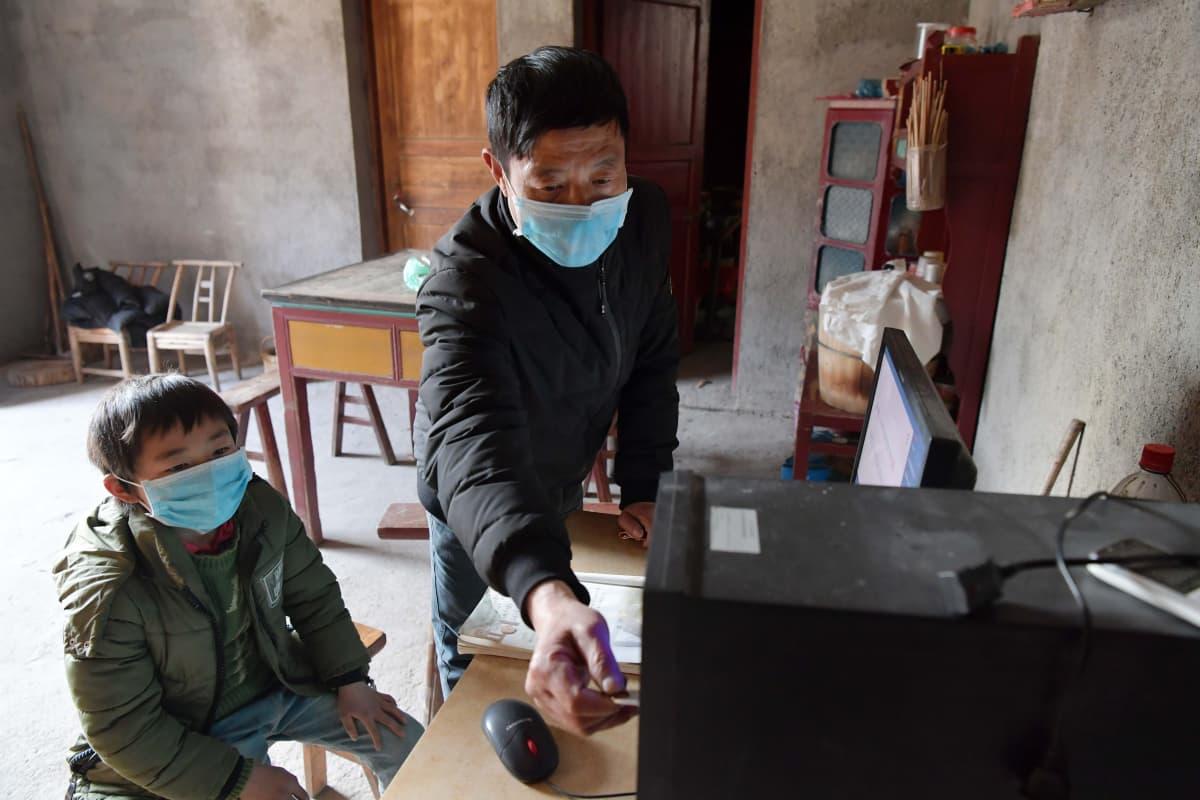 Xinzhun alakoulun rehtori lataa oppilaan muistitikulle materiaalia etäopiskelua varten itäisen Kiinan Jiangxin provinssissa 17. helmikuuta 2020.