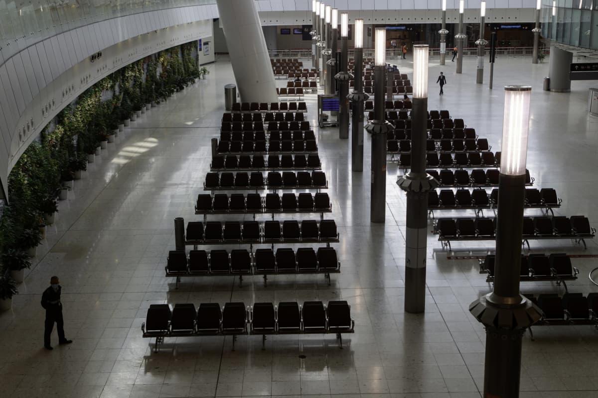 Turvamies vartioi odotushuonetta rautatieasemalla Hongkongissa 28. tammikuuta 2020. Aula on lähes täysin tyhjä.