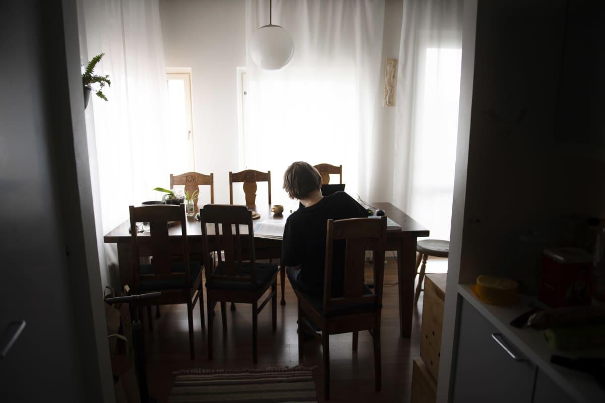 Alakoululainen tekee matematiikan tehtäviä kotonaan.