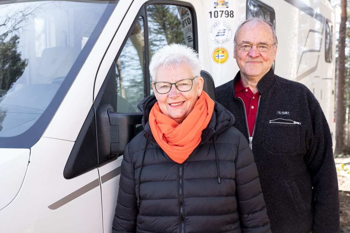 Pentti ja Pirkko Äijö poseeraavat matkailuautonsa vieressä.