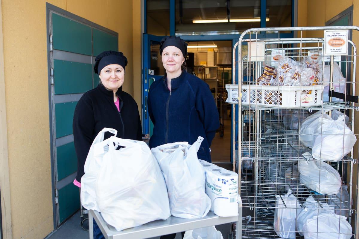 Inga Varul (vas.) ja Kirsi Salmi  jakoivat ruokakasseja tarvitseville Sääksjärven koululla 27.3.2020.