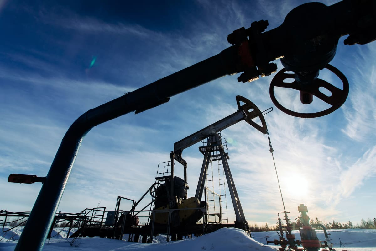Öljyntuotantolaitteita lumisessa maisemassa.
