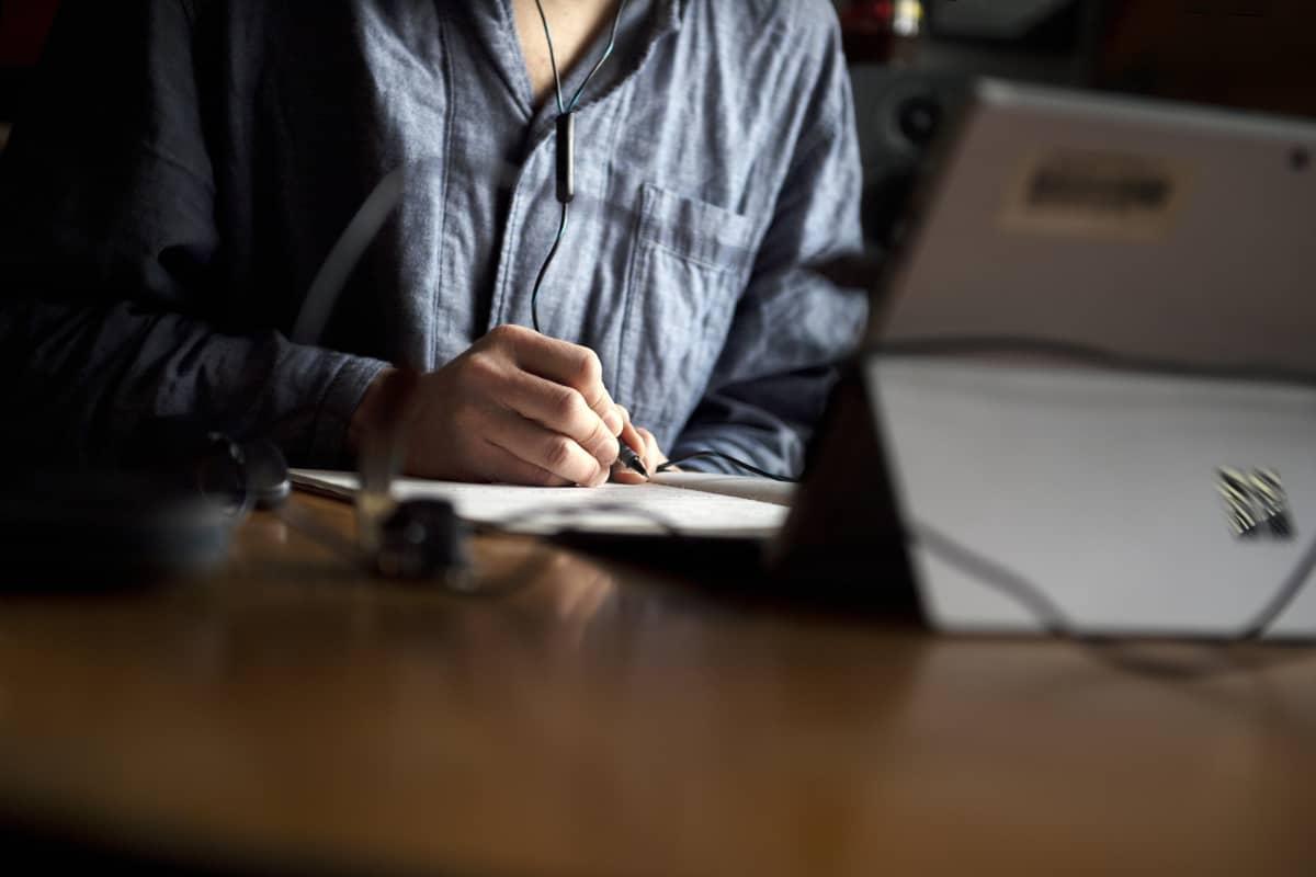 Pyjamapukuinen mies työskentelee kotonaan.