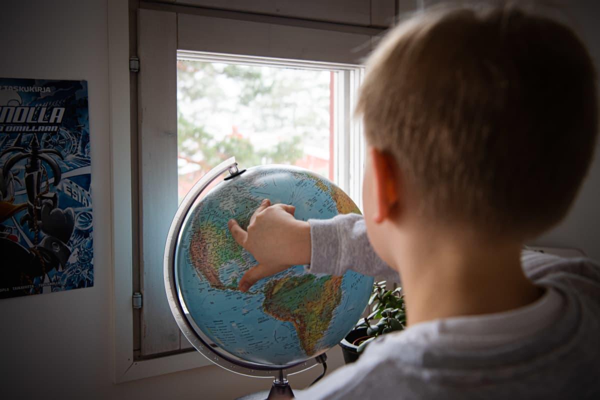 Lapsi tutkii karttapalloa huoneessaan.