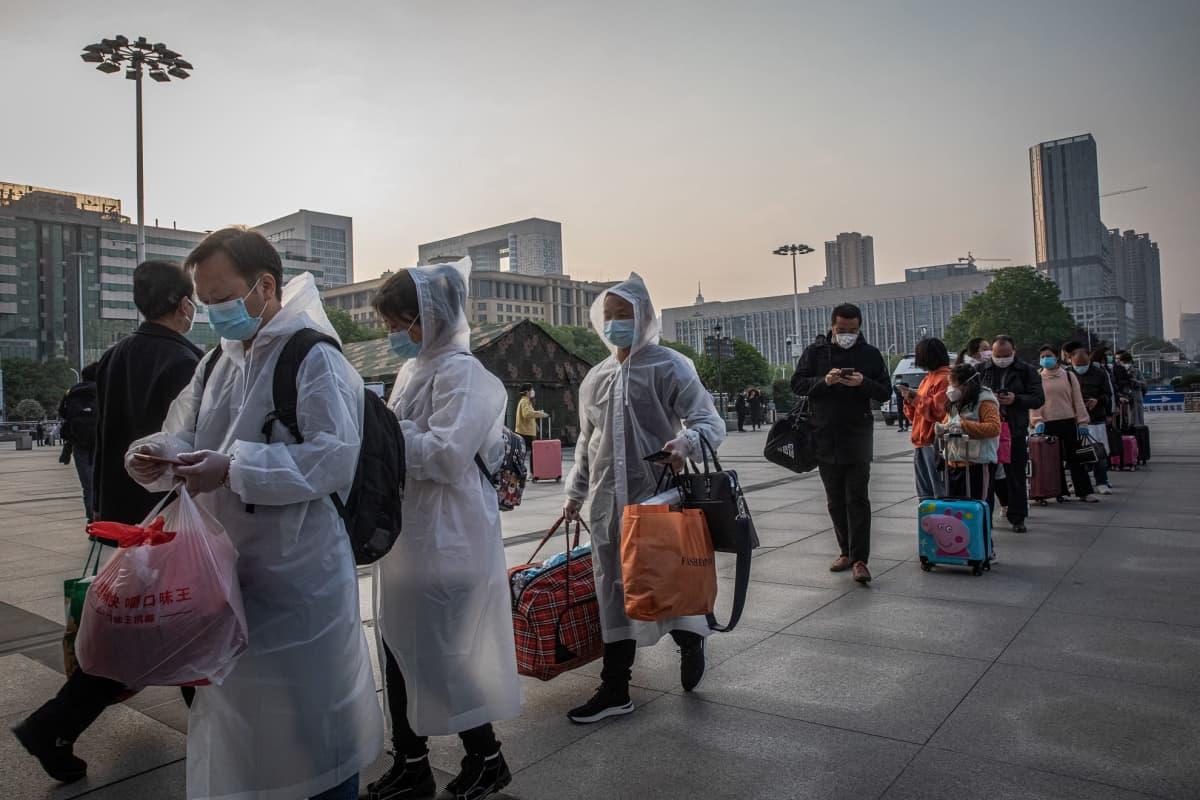 Ihmiset jonottivat Wuhanissa keskiviikkona pääsyä rautatieasemalle, kun kaupungin eristys purettiin kuukausien jälkeen.