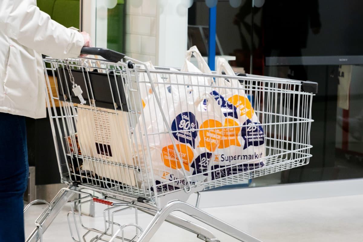 Nainen työntää ostoskärryä jossa monta kassillista ruokaostoksia.