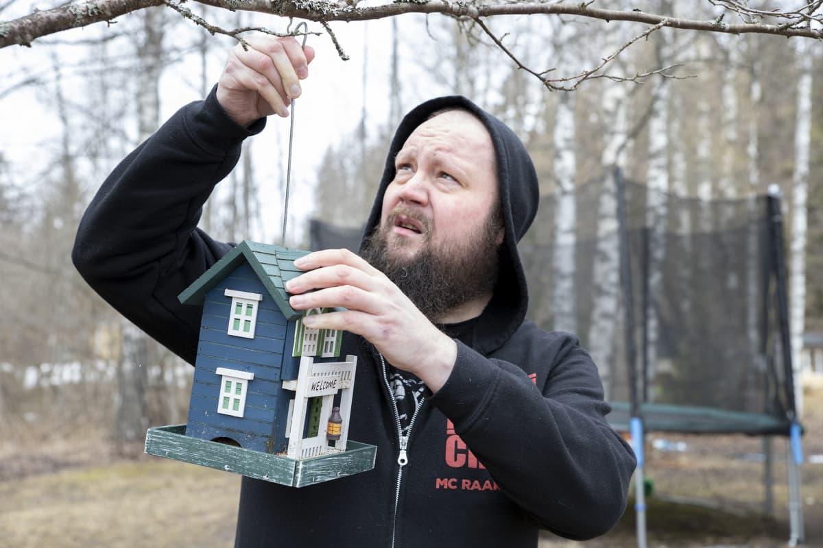 Muusikko Petja Turunen asettelee lintulautaa puunoksaan.