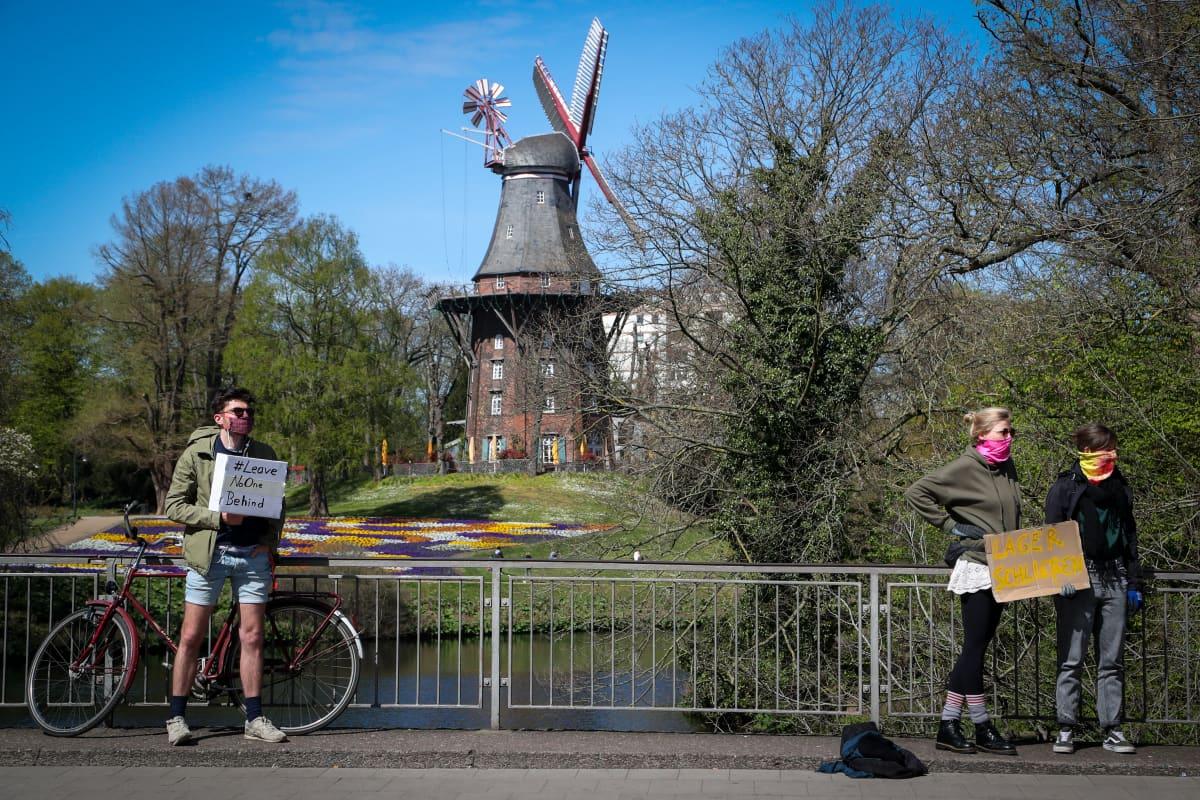 Mielenosoittajan kyltissä vedotaan turvapaikanhakijoiden oikeuksiin ja elinolosuhteisiin koronakriisin keskellä. Mielenosoittajat pitivät turvavälin ohjeiden mukaisesti Bremenissä Pohjois-Saksassa.