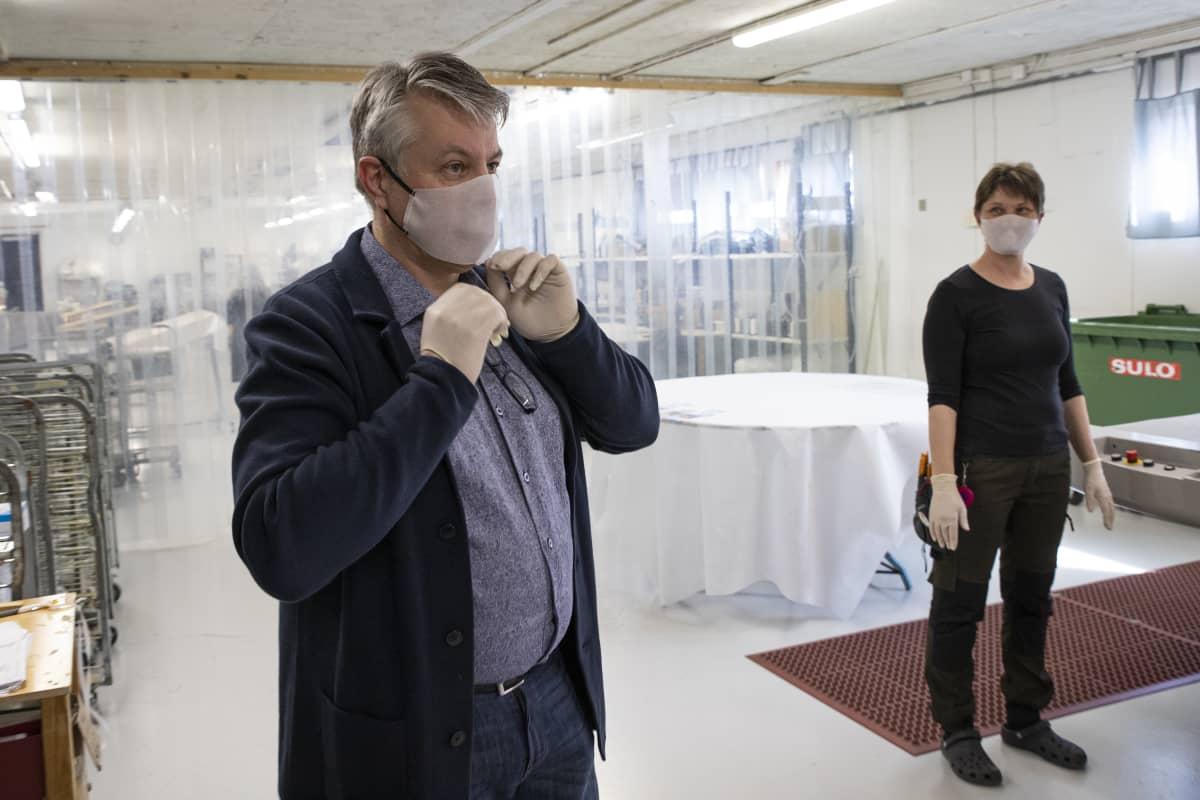 Rautalammilla toimivan Sepon Kalusteen toimitusjohtaja Ismo Noronen ja leikkaaja Katja Korhonen suojaimet kasvoillaan.