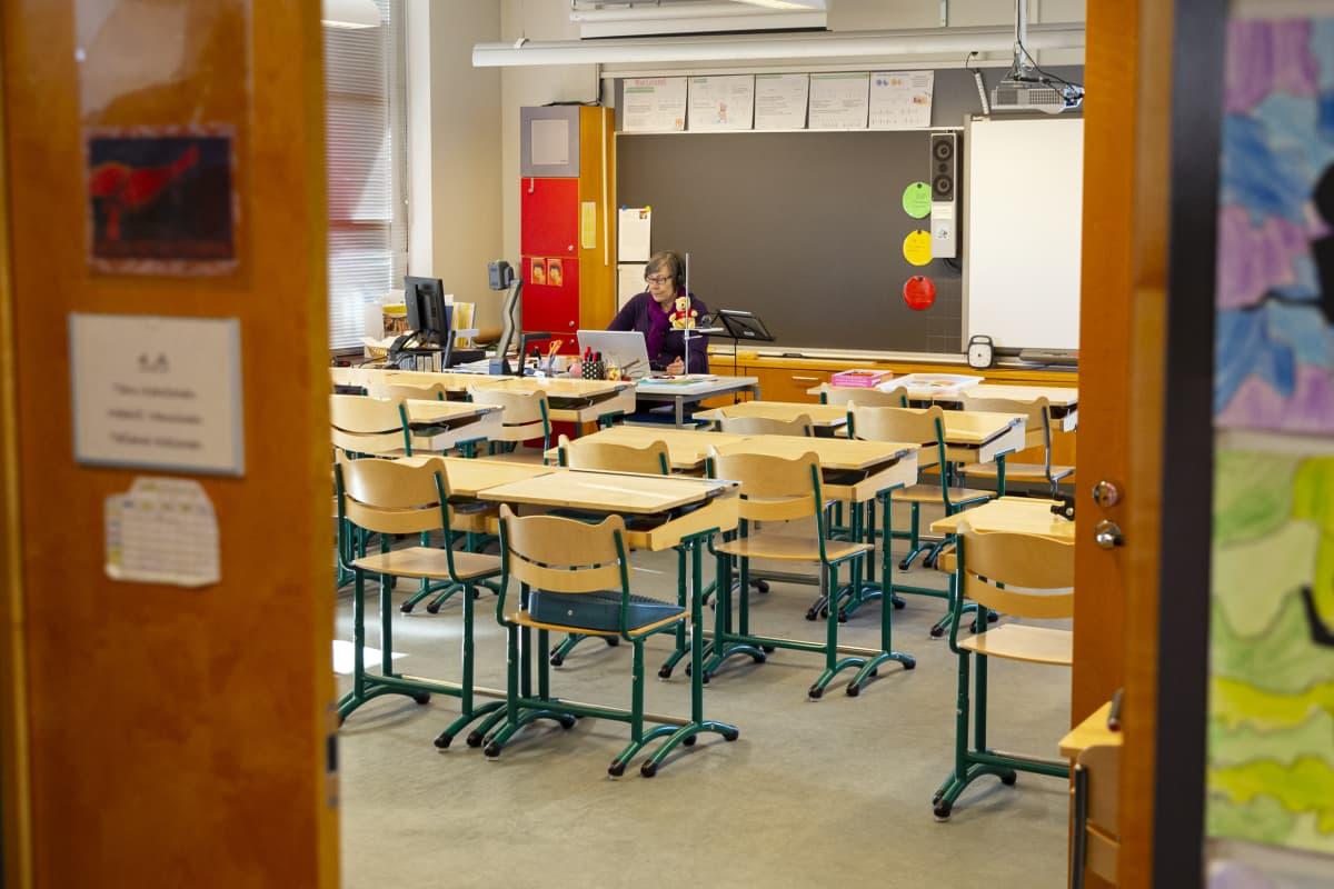 Luokanopettaja Taru Kantonen pitämässä etäopetusta tyhjässä luokkahuoneessa.
