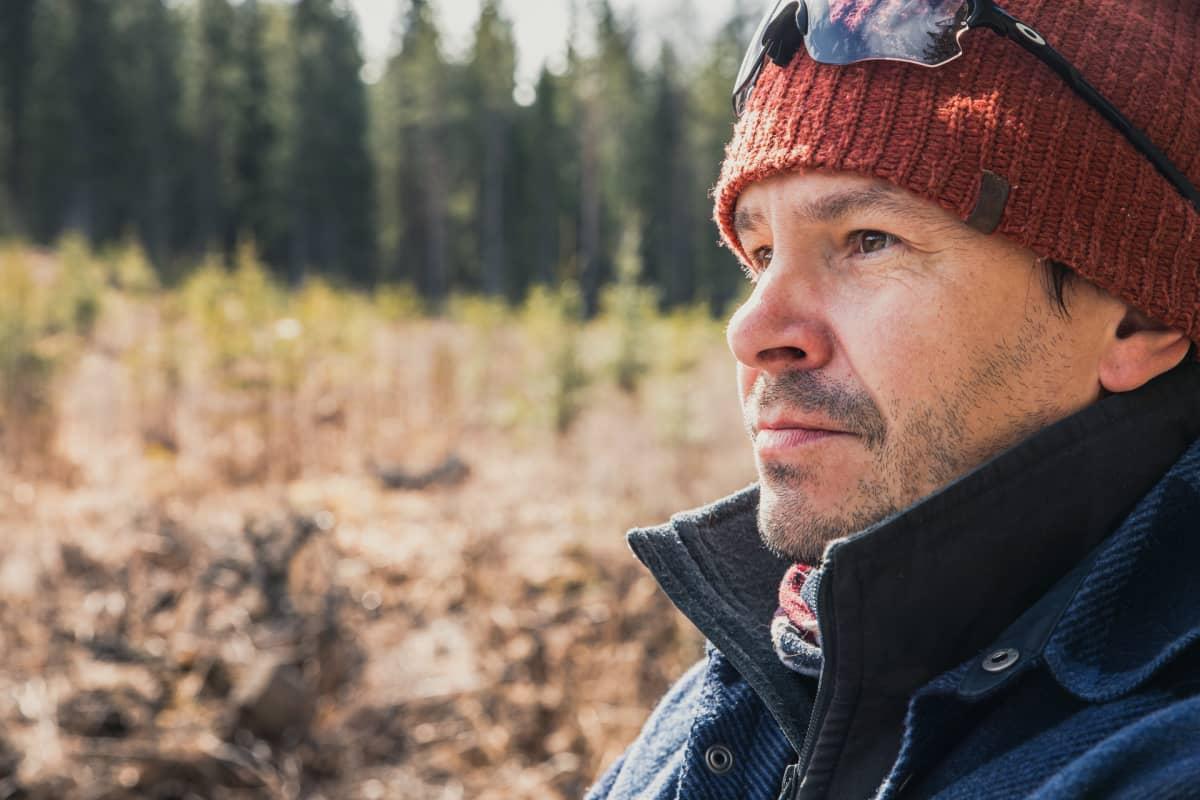 Mies katsoo metsään