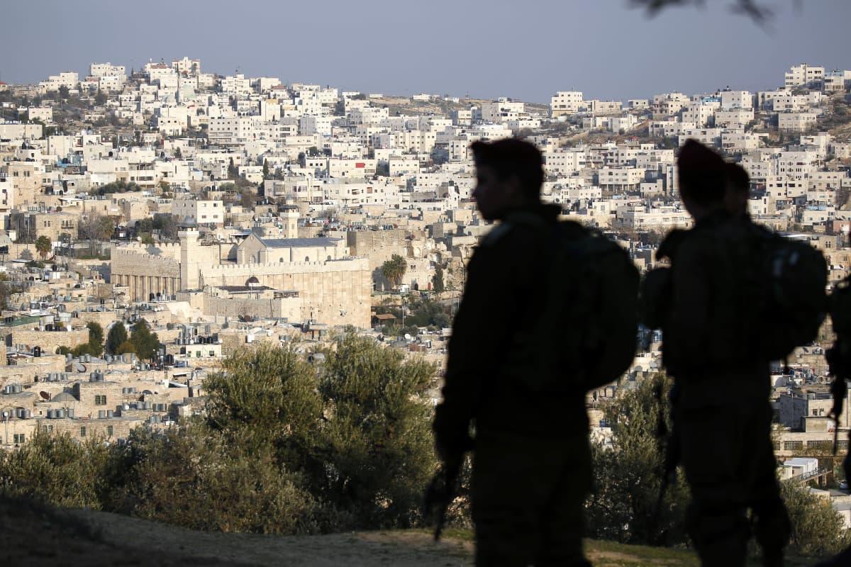 Kaksi israelilaissotilasta partioi. Taustalla näkyy Hebron ja Patriarkkojen hauta.