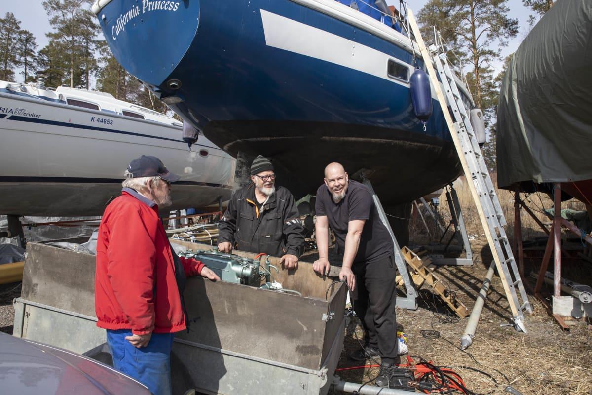 Miehet korjaavat venettä.