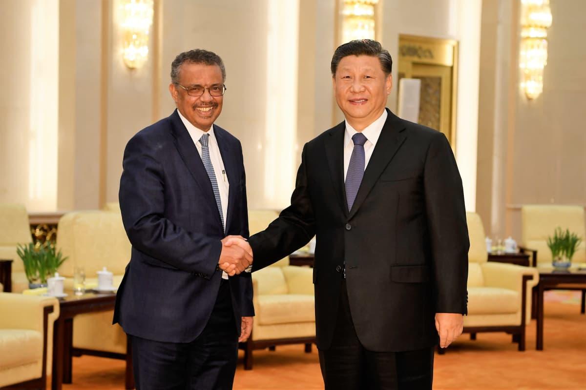 WHO:n pääjohtaja ja Kiinan presidentti kättelevät hymyillen. Miehillä on tummat puvut ja siniset kravatit. Taustalla näkyy salia.