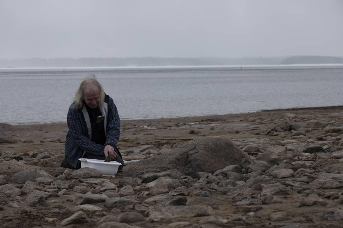 Arkeologi Tapani Rostedt kaivaa kuoppaa Kiantajärven rannalla.