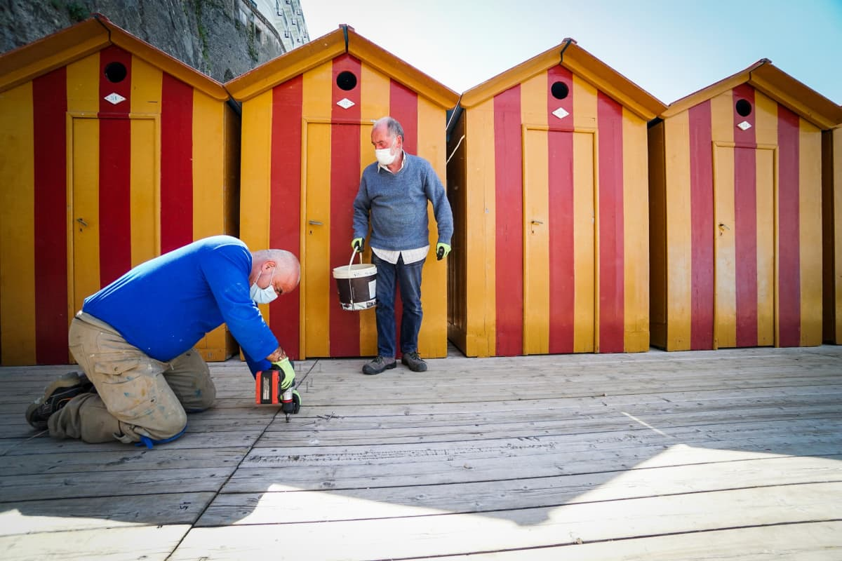 Mies poraa laiturin lankkua polvillaan värikkäiden uimakoppien edessä, toinen seisoo vieressä ämpäri kädessään