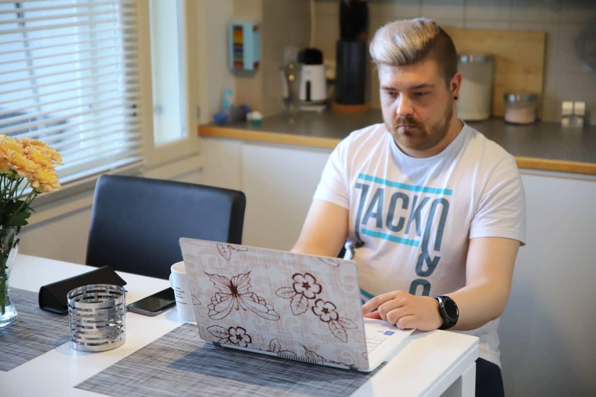 Eetu Louhe istuu keittiössää ja käsittelee valokuvia kannettavalla tietokoneellaan.