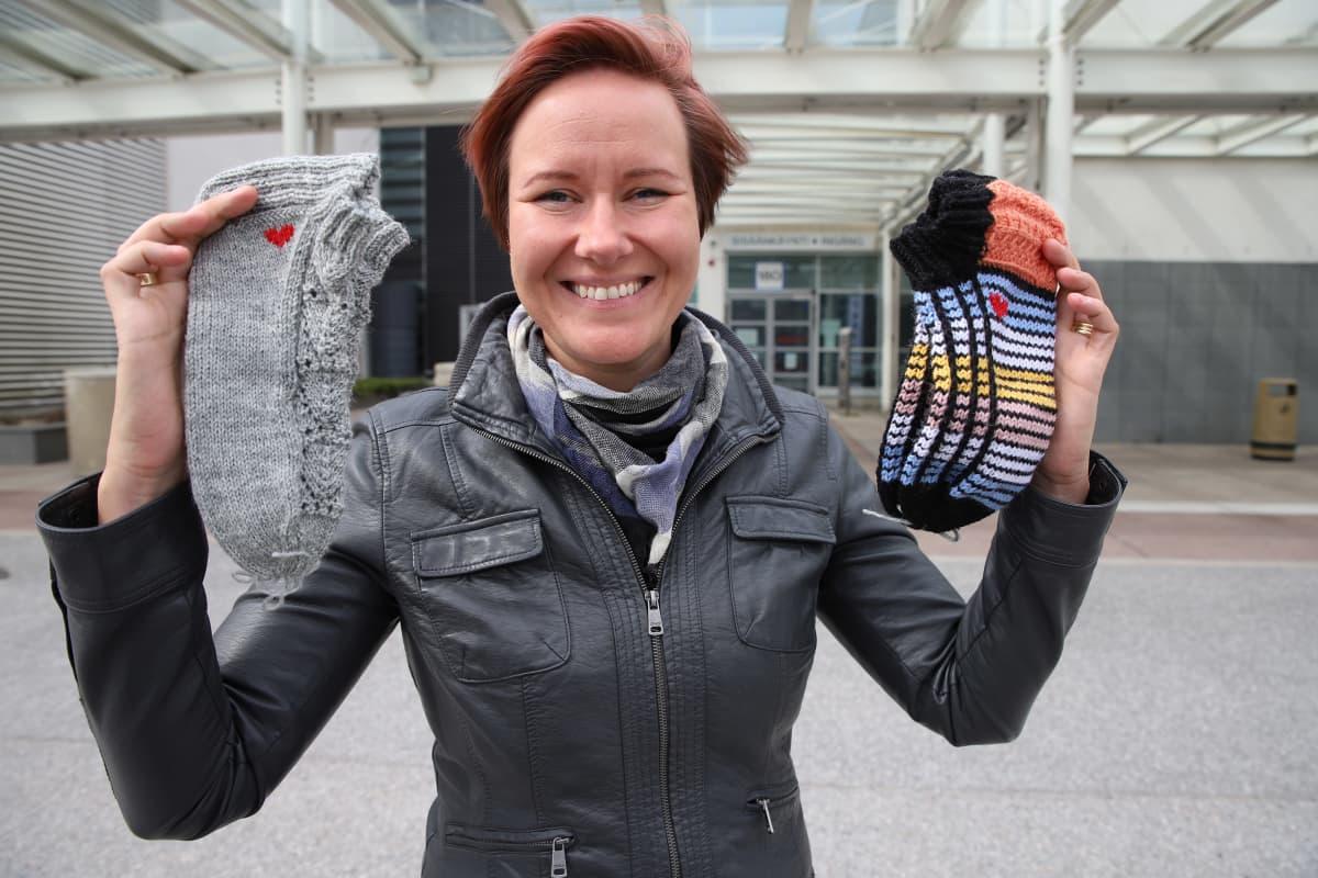 TYKSin aikuisten teho-osaston sairaanhoitaja Soile Ranne esittelee lahjoitettuja villasukkia.